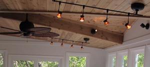 Beadboard ceiling in sunroom with track lighting