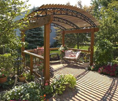 Archadeck pergola with arched roof that serves as a sitting area for this lovely garden