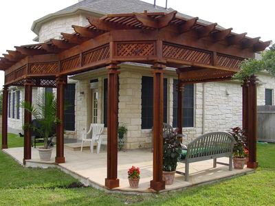 This pergola is more ornate at the top and is finished in a dark brown stain