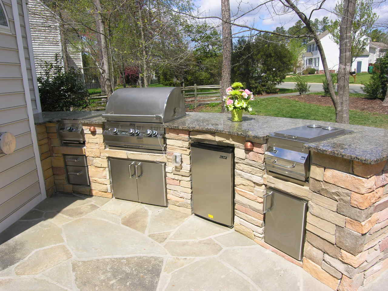 this custom outdoor kitchen design has space for several outdoor chefs