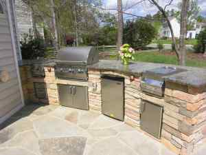 This custom outdoor kitchen design has space for several outdoor chefs to help prepare dinner